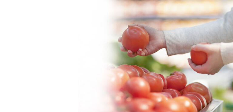 Consumer selecting tomatoes at a grocery store
