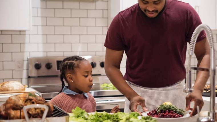 father and young daughter prepping Thanksgiving dinner together