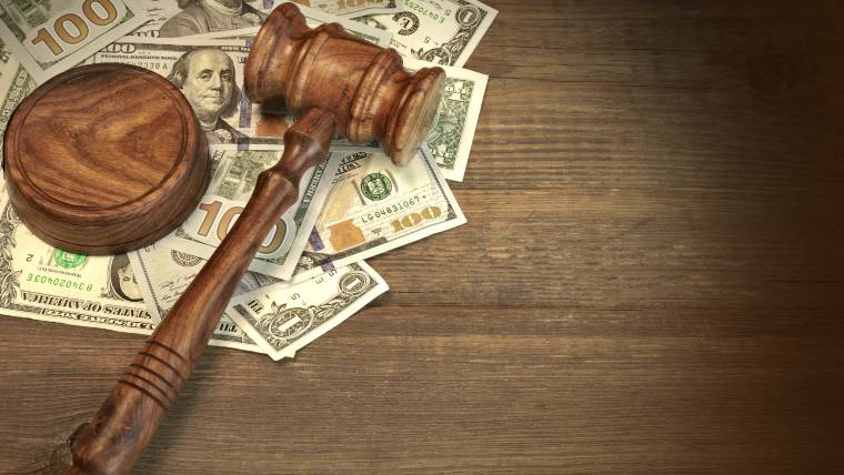 Gavel and money on wood surface