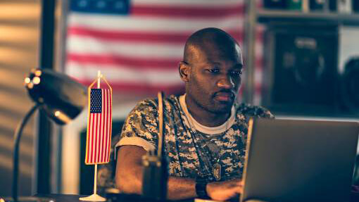 Military servicemember using a laptop