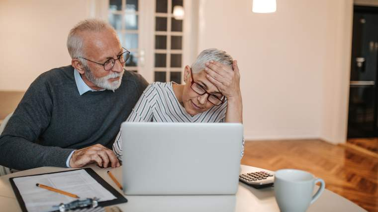 concerned senior couple reviewing information on their laptop