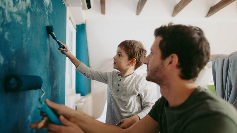 father and son painting wall together