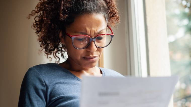 woman reading a document and seemingly feeling confused