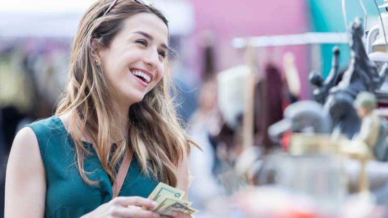 Young woman holding small amount of cash
