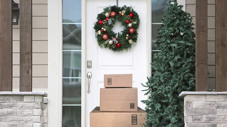 stack of delivery boxes under a Christmas wreath on a doorstep
