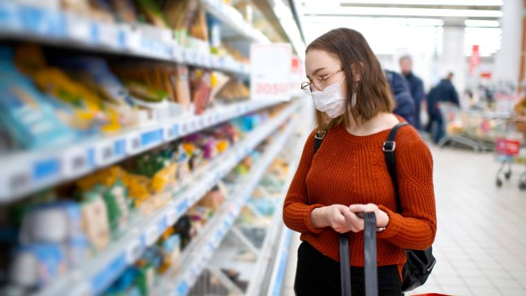 young woman shopping for groceries with a mask on