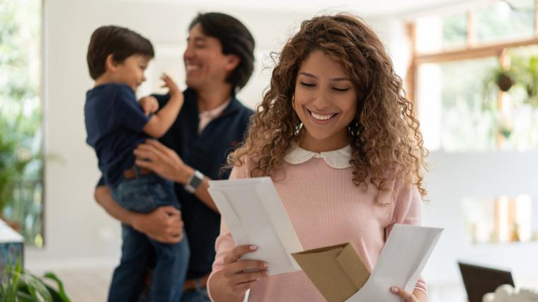 woman opening mailing with husband and small child in the background