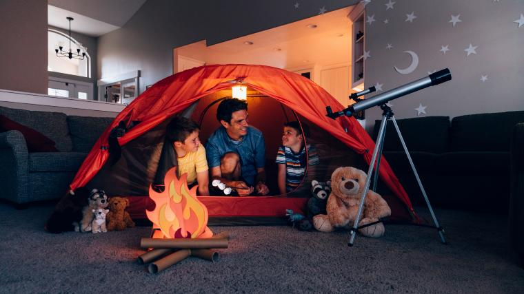 Father camping indoors with his young kids