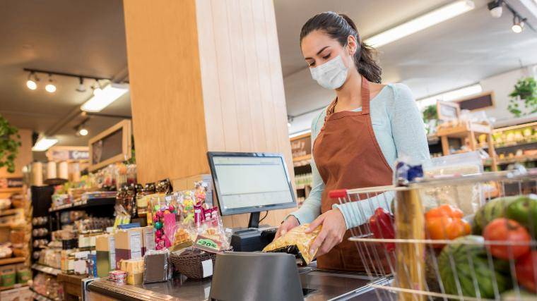 cashier in grocery wearing face covering