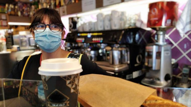 barista wearing a mask and cashing out customer