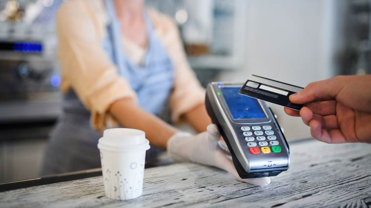 using a credit card at a coffee shop