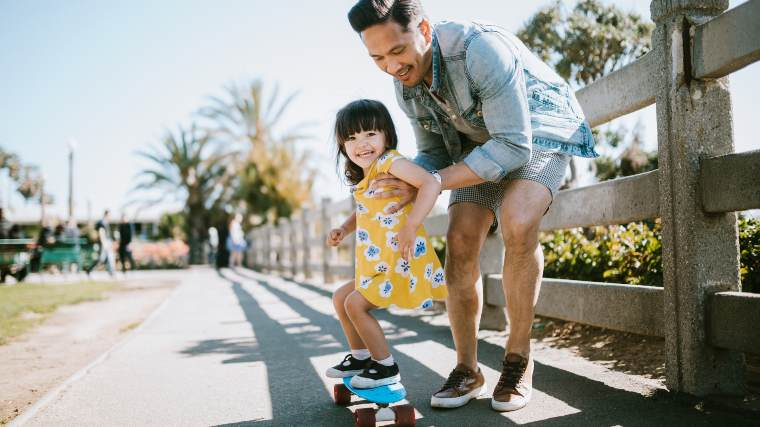 A father teaching his young daughter how to skateboard.