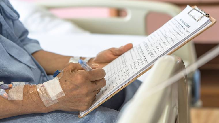 The hands of an elderly patient in a hospital as they sign paperwork.
