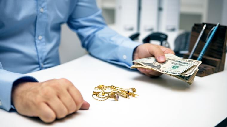 man purchasing jewelry at a pawn shop