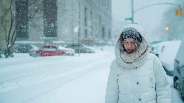 woman walking through city during major snow storm